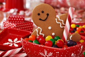 Fun image of smiling gingerbread man with peppermint stick in holiday snowflake dish with colorful candy